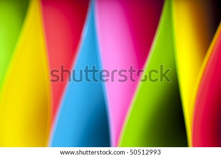 Colorful abstract and macro image of card stock in unique elliptical shapes with shadow effect and selective focus on a black background.  Image taken with slight blur for additional effect.