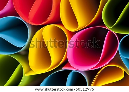 Colorful abstract and macro image of card stock in unique elliptical shapes with shadow effect and selective focus on a black background.