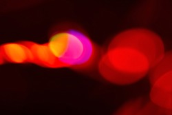Colorful abstract background. Bokeh light. Blur glow. Defocused vibrant neon red orange pink round flecks on dark festive poster with empty space.