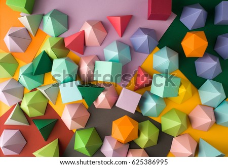 Colorful abstract geometric background with three-dimensional solid figures. Pyramid Dodecahedron prism rectangular cube arranged on colored paper. #625386995