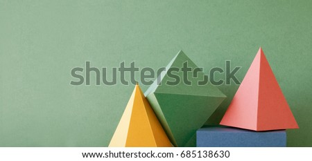 Colorful abstract geometric background with three-dimensional solid figures. Pyramid prism rectangular cube arranged on green paper. Yellow blue pink malachite colored geometrical shapes. Soft focus #685138630