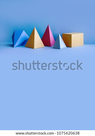 Colorful abstract geometrical composition. Three-dimensional prism pyramid rectangular cube objects on blue background. Yellow blue red green colored solid figures, vertical copy space photo