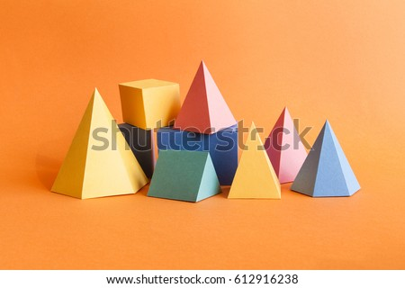 Colorful abstract geometrical composition. Three-dimensional prism pyramid rectangular cube objects on orange paper background. Yellow blue pink green colored solid figures, soft focus photo.
