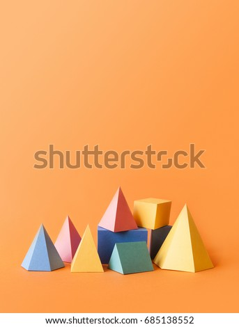 Colorful abstract geometrical composition. Three-dimensional prism pyramid rectangular cube objects on orange paper background. Yellow blue pink green colored solid figures, vertical copy space photo