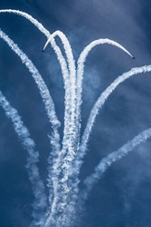 colorful acrobatic airshow of a team of pilots flying jets on formations with colorful smokes venting from the plane.