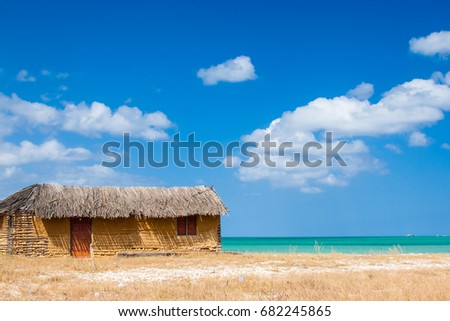Colorful adobe house next to the sea under blue sky #682245865