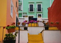 Colorful adobe houses with stucco walls and geranium flower pots on Avenida Hidalgo in Atlixco, Puebla Mexico.