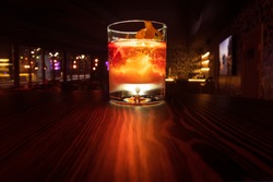 Colorful alcohol cocktail with a warm backlight on a wooden table. Served with ice and orange peel. Boulvardier or Negroni. Frozen glass.