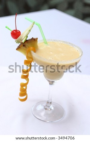 Colorful alcoholic cocktail in a martini glass against white background