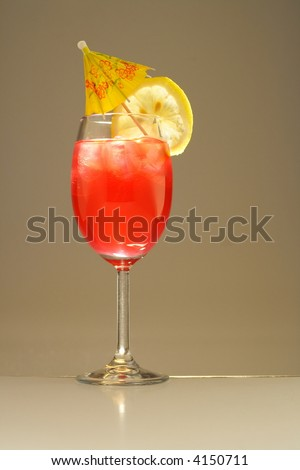 Colorful alcoholic cocktail in a tall glass with lemon and umbrella  against white background