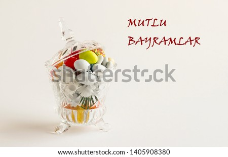 Colorful almond candies in the stylish,crystal candy bowl.The Sugar Feast concept. Writing near Happy Holidays in Turkish .