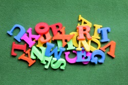 Colorful Alphabet magnetic letters on green background