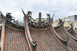 Colorful ancient dragon statues, typical asian fantasy style, with religious art ornament and oriental decoration on old roof of taiwanese Mazu Zhunan Wugu Xiandi Temple, Miaoli City, Taiwan, Asia.