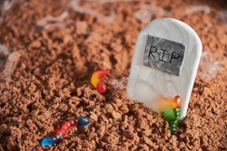 Colorful and bright gummy worms in chocolate cake ground around a sugar gravestone, halloween party fun food