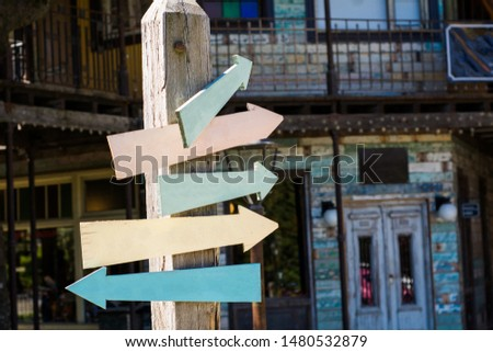 Colorful and empty wooden signpost indicating directions outdoors. #1480532879