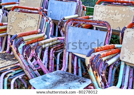 Colorful and rusty old chairs stacked