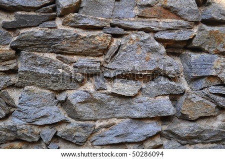 Colorful and textured stone masonry wall useful for backgrounds