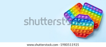 Colorful anti-stress fidget push pop it sensory toys for childrenisolated on blue background. Simple dimple. Top view, flat lay, copy space. Selective focus. Photo stock ©