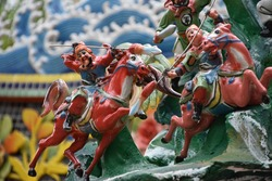 Colorful antique small soldier figures on horses, asian fantasy style, with traditional art ornament and religious decorations on roof of old taiwanese spiritual temple shrine in Taipei, Taiwan, Asia.