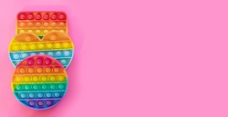 colorful antistress sensory toy fidget push pop it on pink background