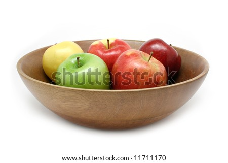 Colorful apple assortment in a wooden bowl isolated on white