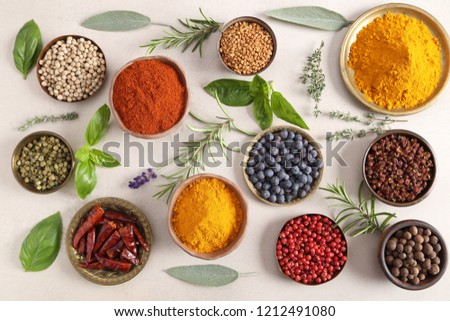 Colorful, aromatic spices and fresh herbs on a light background. Top view. #1212491080