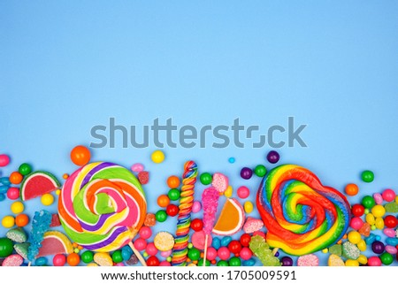 Colorful assortment of candies. Top view bottom border on a blue background. Stock foto ©