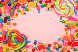 Colorful assortment of candies. Top view frame over a pink background.