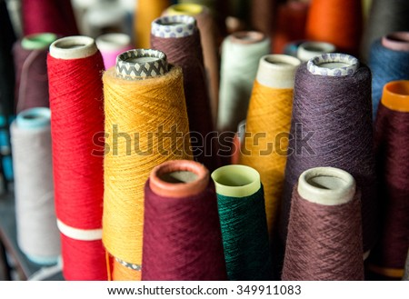 Colorful assortment of vivid colors of cotton spools on cardboard cones for use in the knitwear and garment industry viewed high angle #349911083