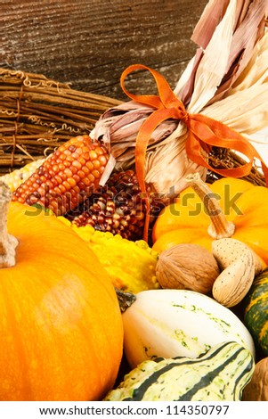 Colorful autumn harvest vegetables make a colorful Fall decoration sitting in a basket against a wood background