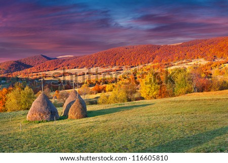 Colorful autumn landscape in the mountains village. Sunset