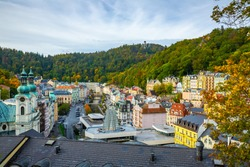 Colorful autumn landscape of Karlovy Vary central area with church of St. Mary Magdalene and hot spring colonnade, Czech Republic