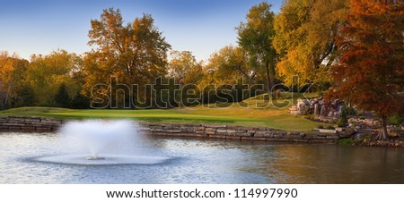 Colorful Autumn landscape with a flowing fountain in the water.