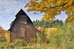 Colorful autumn leaves framing wooden barn with fragments of tattered American flag hanging from hayloft door.