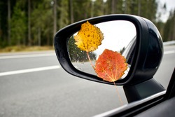 Colorful autumn leaves on the sideview, rearview mirror of a car on road