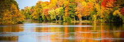 Colorful autumn trees reflecting off of the Wisconsin River in Merrill, Wisconsin, panorama
