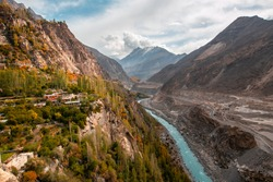Colorful autumn view of Hunza from Altit fort show blue river flowing along the road through Karakoram mountain range, Gilgit-Baltistan, Pakistan.