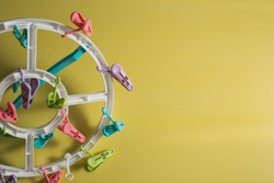 Colorful baby clothes hangers, clothes clips isolated on yellow background, JPEG large file