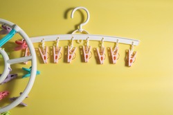 Colorful baby clothes hangers with clips in colors isolated on yellow background.