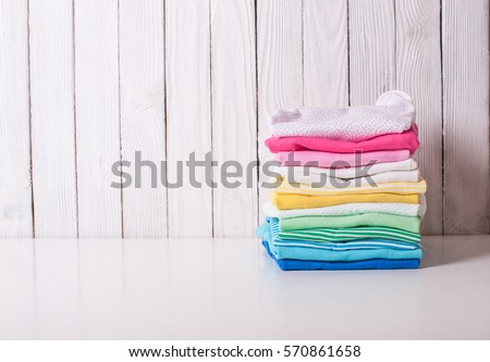 Colorful baby clothes of folded pile on a white background