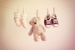 Colorful background for baby girl with two pink socks, sneakers and teddy bear with copy space.