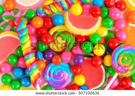 Colorful background of assorted candies including gum balls, lollipops and jelly candies