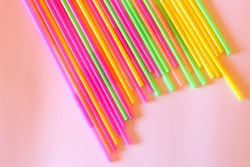 Colorful background. Vivid flatlay. Multicolored plastic drinking cocktail straws on a white background. Colorful design and abstract. Bright multicolored beverage tubes. Make a cocktail.