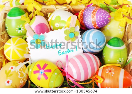 colorful background with easter painted eggs and greeting card  in wicker basket