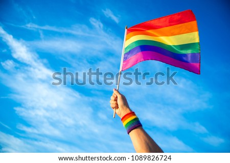 Colorful backlit rainbow gay pride flag being waved in the breeze against a sunset sky.