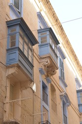 Colorful balconies of ancient building in Valletta, Malta. This medieval city is built from the light sandy color stones, and colorful balconies make it look vibrant and cozy.