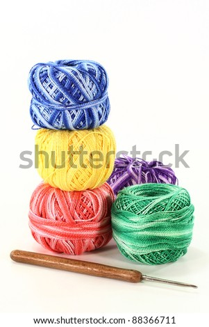 colorful ball of wool and crochet hook on a white background