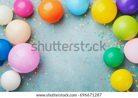 Colorful balloons and confetti on blue table top view. Festive or party background. Flat lay style. Copy space for text. Birthday greeting card.