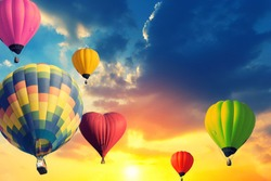 Colorful balloons floating in the sky at sunset.
