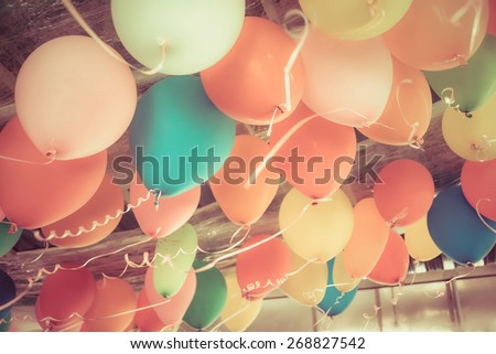 Colorful balloons floating on the ceiling of a kid party celebration in vintage retro color style